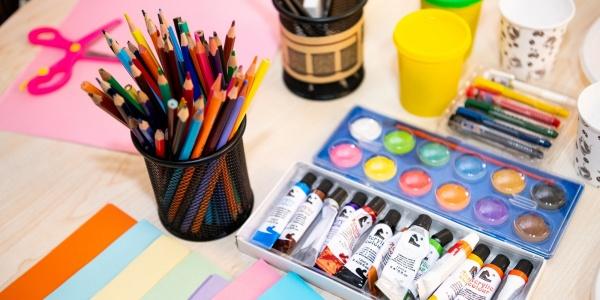 tavolo con pastelli colorati e tempere per fare attività manuali per bambini