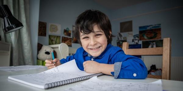 Bambino inglese seduto alla sua scrivania della camera mentre scrive su un quaderno