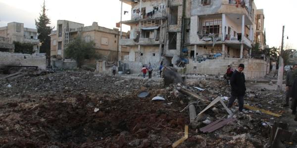 Siria, macerie di palazzi e in sfondo un palazzo semi distrutto dai bombardamenti. Tra le macerie camminano alcuni adulti e bambini.