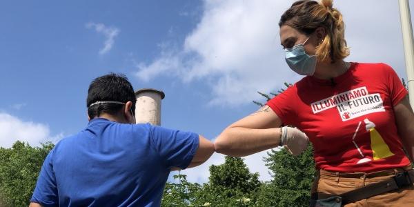 operatrice save the children con maglietta rossa e mascherina mentre si saluta con il gomito con un ragazzo con mascherina