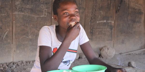 Una bambina seduta a un tavolino mangia da piatti verdi