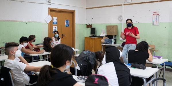 classe di studenti ripresi da dietra seduti ai banchi, in fondo un insegnante in piedi appoggiato alla cattedra spiega