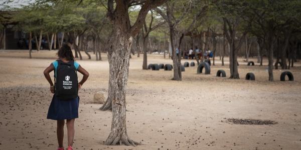 bambina di spalle con lo zaino cammina su terreno vicino a un albero