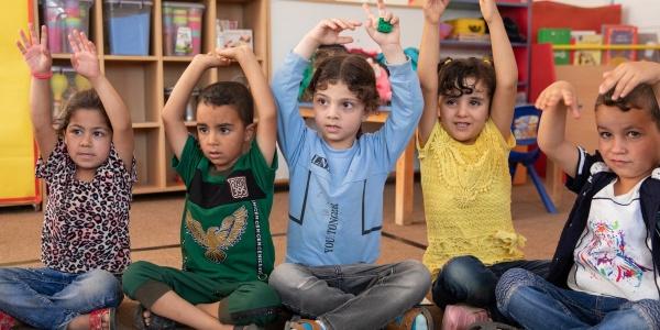 5 bambini seduti in cerchio con le mani alzate durante una lezione a scuola