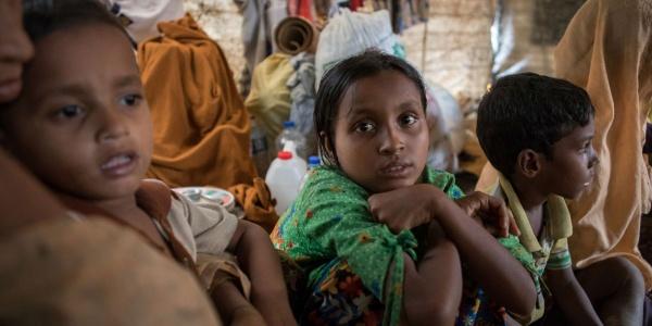Una bambina e due bambini rohingya seduti vicini