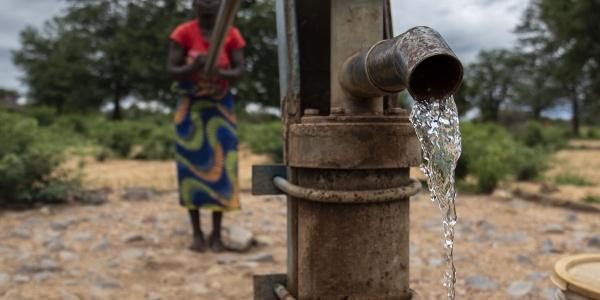 In primo piano una fontana a pompa da cui sgorga acqua, dietro sfocata si vede una donna che aziona la pompa per far uscire l acqua