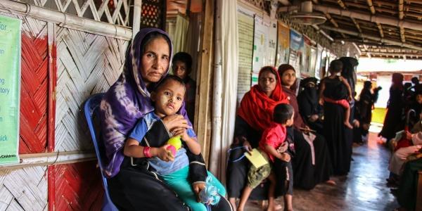 Donna Rohingya tiene in braccio suo figlio seduta in un tendone del campo profughi cox s bazar