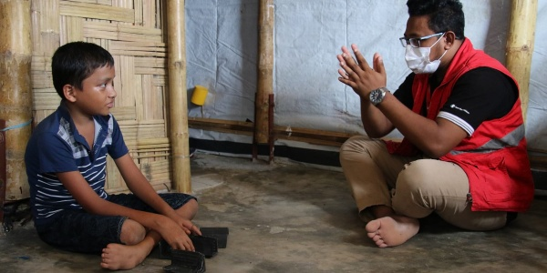 Un bambino rohingya è seduto a terra a gambe incrociate e davanti a lui un operatore di save the children gesticola con le mani.