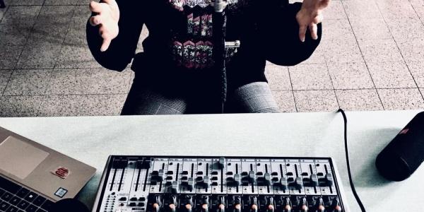 Inquadrata una tastiera per regolare i suoni appoggiata su un tavolo e davanti un ragazzo seduto inquadrato fino al collo e tiene lee mani sollevate verso l alto