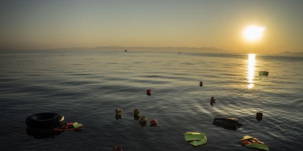 resti di giubbotti salvagente e gommoni galleggiano in mare al tramonto
