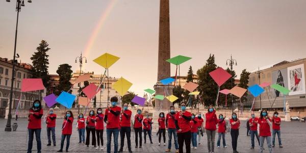 persone con maglietta rossa azione con aquiloni a roma davanti ad un arcobaleno