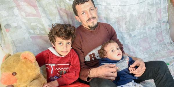 Un padre con i due figli, uno seduto accanto a lui, l altro più piccolo è in braccio a lui.