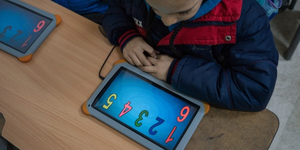 bambino seduto al banco studia con un tablet davanti