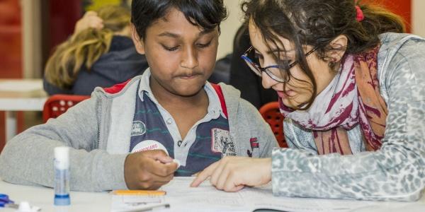 due ragazzi seduti a un banco di scuola fanno i compiti insieme