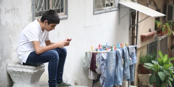 Un ragazzo adolescente seduto su un sedile di marmo è piegato a guardare il suo cellulare. Indossa un paio di jeans, scarpe verdi e una maglietta bianca. Accanto a lui uno stendino con i panni stesi.
