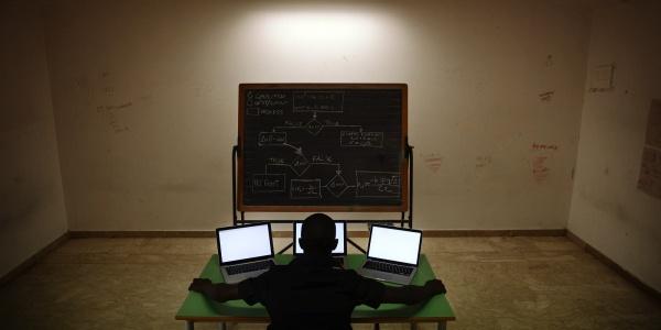 Ragazzo di spalle seduto al tavolo con tre computer