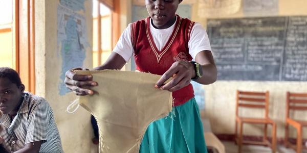 Ragazza ugandese in divisa scolastica tiene in mano slip autoprodotti.