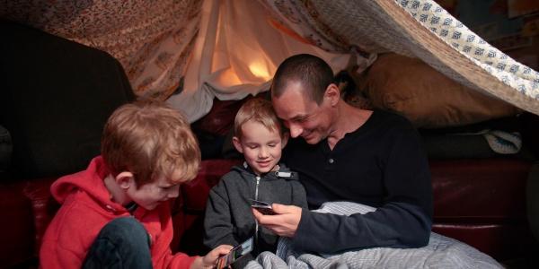 Papà con i propri figli in una tenda che giocano
