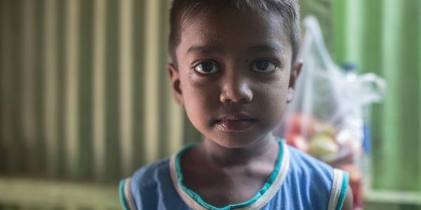 Mezzo busto di un bambino indiano che indossa una canottiera blu con colletto giallo.