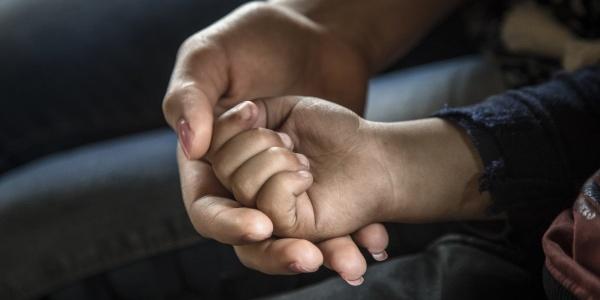 Primo piano di mano di donna che tiene nella sua la mano di un bambino piccolo