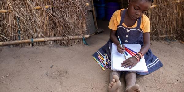 una bambina africana con maglietta gialla e vestito jeans è seduta a terra accanto alla sua capanna mentre è intenta a scrivere qualcosa sopra un quaderno