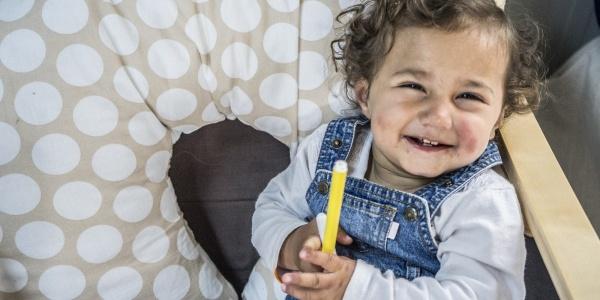 bambina bianca con i capelli ricci seduta con in mano un pennarello giallo