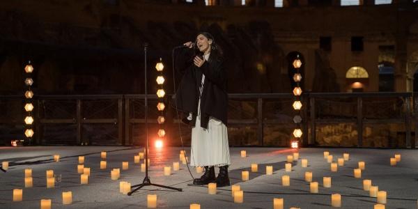 La cantautrice Elisa canta in piedi con microfono all interno del Colosseo circondata da candele accese sul palco. Elisa indossa un vestito lungo bianco e una giacca lunga nera