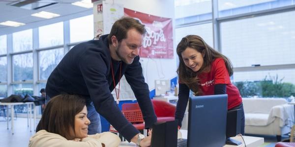 Tre operatori Save the Children guardano un pc appoggiato su un tavolo