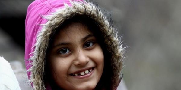 bambina con cappotto rosa e cappuccio che ride