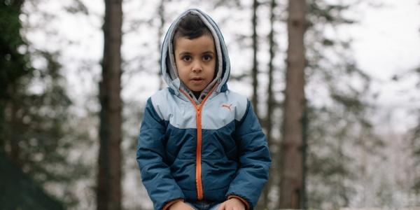 Bambino seduto su un muretto e sguardo in camera con sfondo bosco innevato