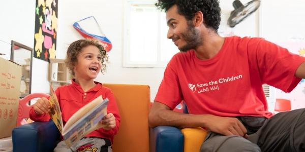 operatore save the children ascolta una bimba che legge sorridente