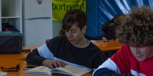 due ragazzi seduti a un banco in un aula di un punto luce stanno facendo i compiti di scuola