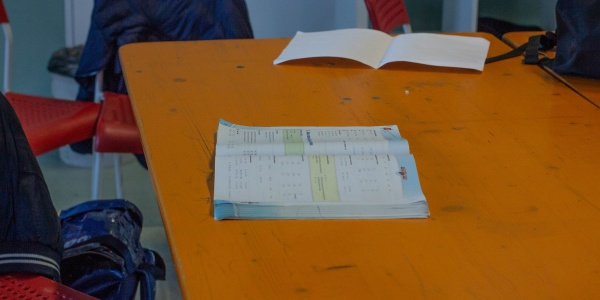 Tavolo con libri aperti sopra e sedie vuote intorno