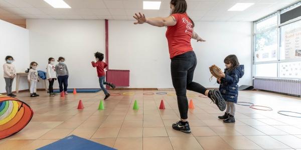 operatrice save the children gioca con alcuni bambini e bambine piccoli in uno spazio mamme