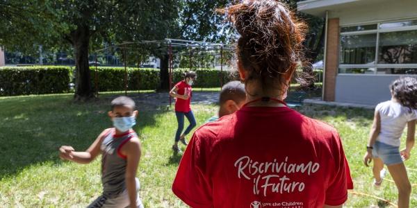 ragazza di spalle con maglietta rossa insieme a dei bambini che giocano nel prato con indosso la mascherina