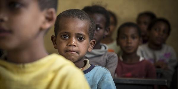 Primo piano di un bambino etiope con maglietta azzura che compare dietro al viso di un altor bambino davanti a lui che si vede sfocato