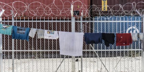recinzione in metallo bianco con filo spinato e panni stesi