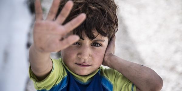 primo piano bambino libanese con mano in primo piano aperta davanti al volto
