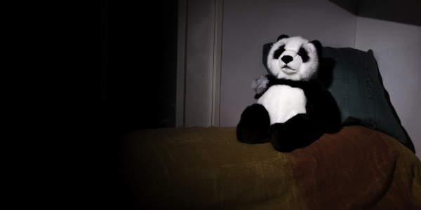 Pupazzo panda con braccio staccato sul letto
