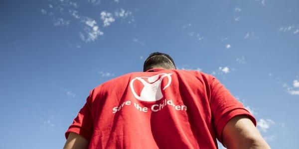 Operatore save the children di spalle con il cielo di sfondo