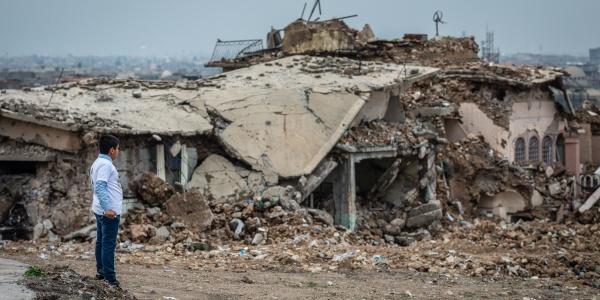 Un bambino iracheno guarda da lontano le macerie di abitazioni distrutte a Mosul
