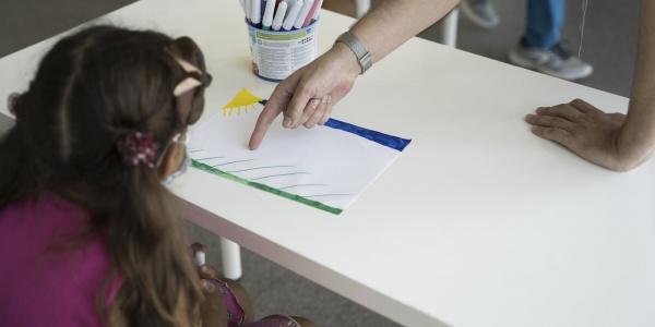 Bambina con codini seduta presa di spalle davanti a un tavolo bianco e davanti a lei c è il braccio di un adulta che indica un foglio sul tavolo