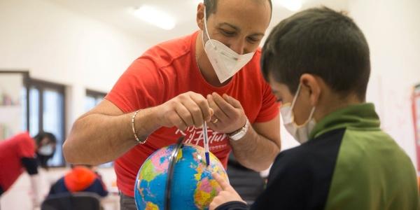 Operatore Save the Children mostra un dettaglio sul mappamondo a un bambino seduto di fronte a lui.