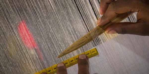 dettaglio di mani che creano un vestito su un telaio