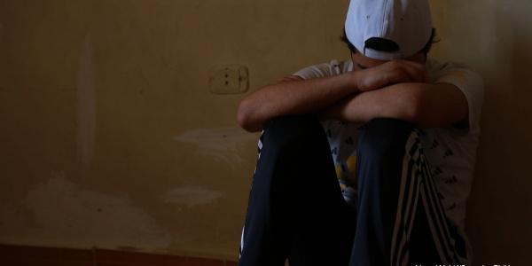 Un ragazzo rifugiato siriano seduto a terra appoggia la testa al braccio e la schiena al muro
