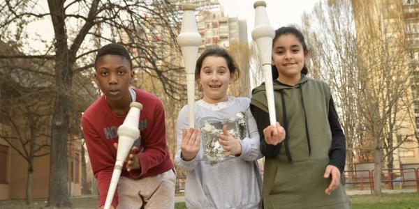 foto all aperto di 3 bambini con birilli in mano che giocano
