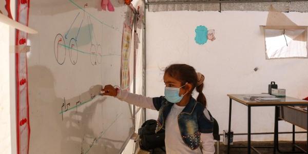 bambina scrive su una lavagna bianca in un aula, indossa una mascherina chirurgica per proteggersi dal Covid-19