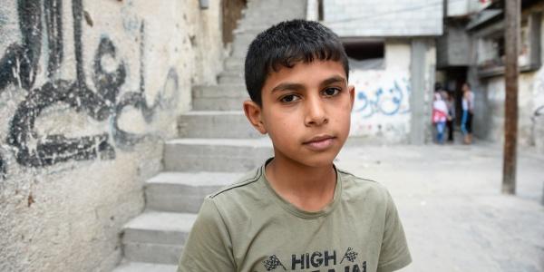 Mezzo busto di un bambino palestinese con maglietta grigia