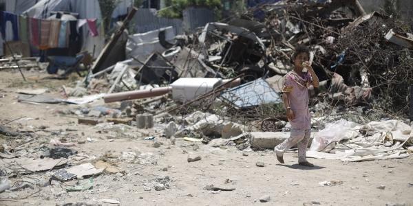 bambina palestinese cammina davanti a un cumulo di spazzatura.