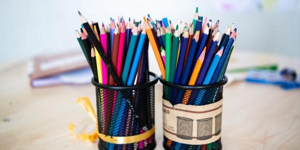 dettaglio su due portamatite pieni di matite colorate